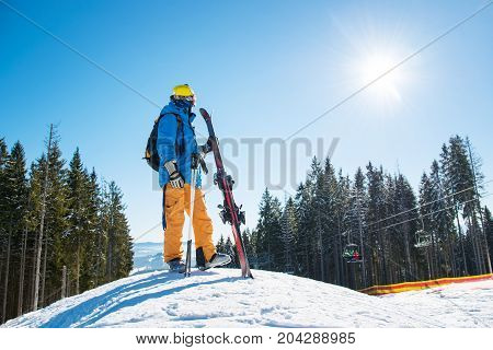 Full Length Shot Of A Skier Standing On Top Of A Snowy Slope In The Mountains Looking Around Enjoyin