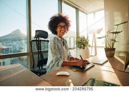 Smiling female designer sitting at her desk. Afro american young woman at her creative workplace.