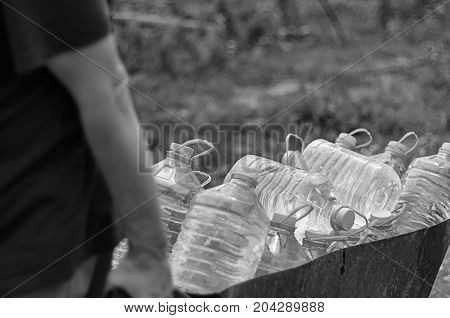 Climate change and water supply shortage threats. White male pulls a cart of plastic bottles filled with clean water from a public pump to his family's house.
