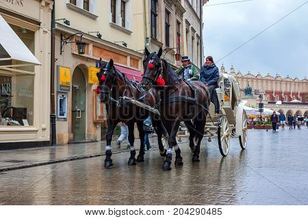 KRAKOW, POLAND - JUNE, 2012: Coachmen with harnessed horse await tourists wishing to admire the city during the ride
