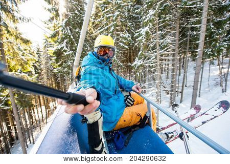 Shot Of A Skier Taking A Selfie With A Selfie Stick While Riding Ski Lift To The Top Of The Mountain