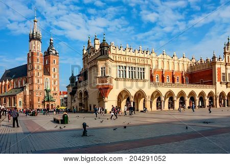 KRAKOW, POLAND - JUNE, 2012: Two major tourist sights St.Mary's Basilica and Cloth Hall on sunny day
