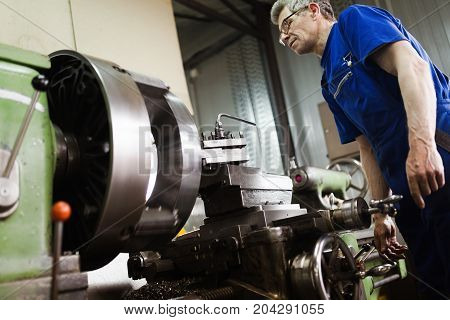 Industrial metal worker working on metal components in metal factory