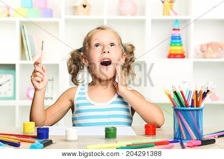 Little Girl Sitting And Drawing At The Table