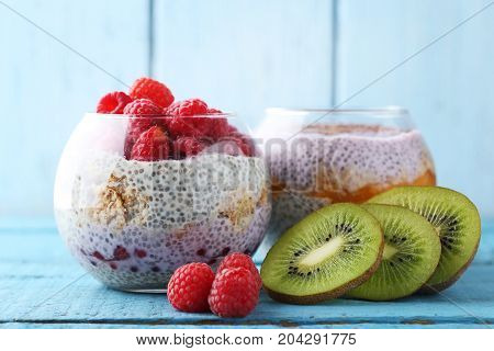 Chia Pudding With Berries In Glasses On Blue Wooden Table