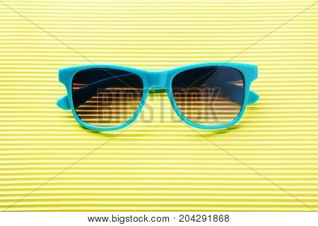 The blue sunglasses on the yellow background