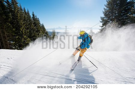 Skier Skiing Downhill In The Mountains. Blue Sky And Winter Forest On The Background Copyspace Sport