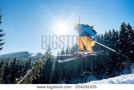 Skier Jumping In The Air While Skiing In The Mountains Blue Sky On The Background Copyspace Sunlight