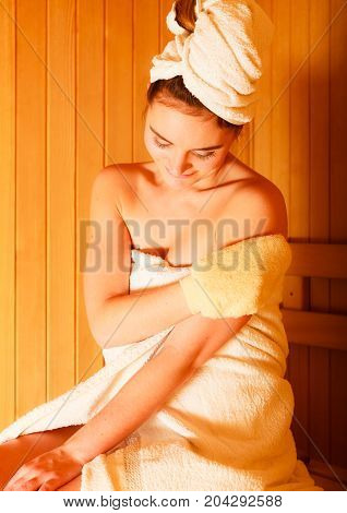 Spa beauty treatment and relaxation concept. Woman white towel relaxing in wooden sauna room making massage with exfoliation glove
