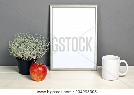 Silver frame mockup with plant pot mug and apple on wooden shelf. Empty frame mock up for presentation design. Template framing for modern art.