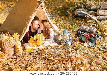 Man and woman hikers camping in autumn nature. Happy young couple backpackers camping in tent, drinking coffee in morning sunny summer day.