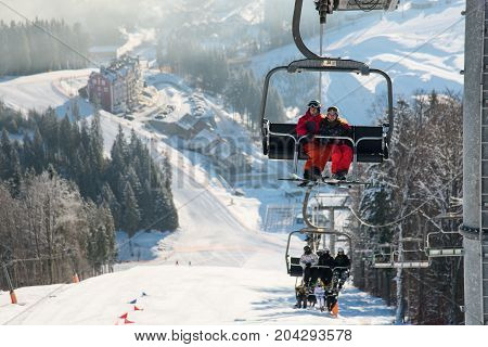 Skiers On The Ski Lift Riding Up At Ski Resort With Beautiful Background Of Snow-covered Slopes, For