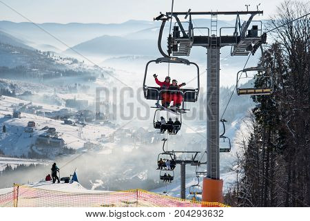 Snowboarders And Skiers On A Ski Lift At Winter Ski Resort With Beautiful Background Of Snow-covered