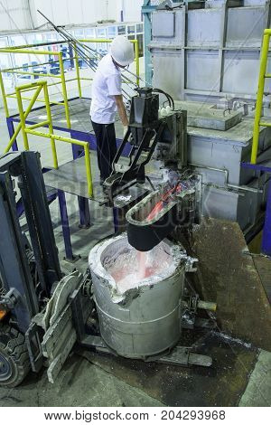 factory worker for the smelting of aluminum metal in the bucket standing on the loading machine