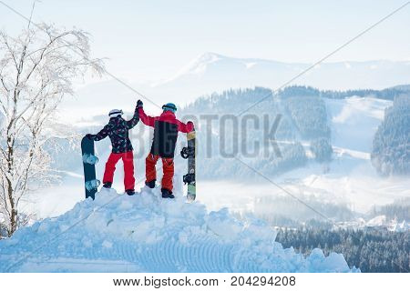 Couple Snowboarders High Fiving Each Other, Standing On Top Of A Snowy Mountain, Observing Stunning