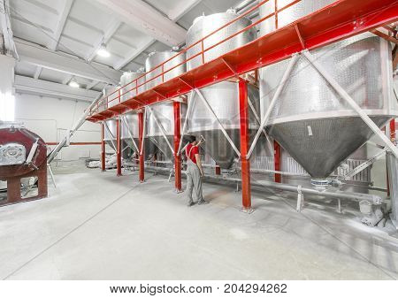 Industrial workshop with large cylindrical containers for the treatment of dry mixes