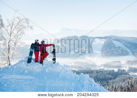 Young Couple Snowboarders Enjoying Beautiful Natural Landscape, Resting On Top Of The Mountain On A