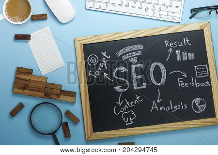 Top view of SEO Search Engine Optimization on black board and graph paper with magnifying glass business object and technology tools money coin on working table
