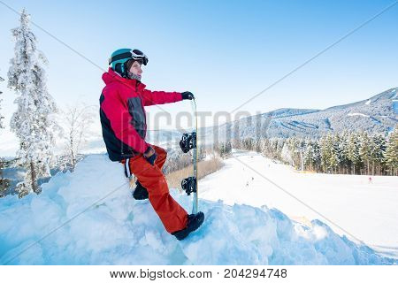 Male Snowboarder Resting On Top Of The Mountain With His Snowboard, Observing Nature At Ski Resort B