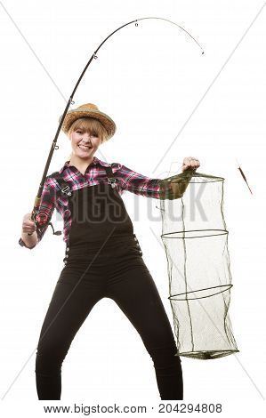 Spinning angling cheerful fisherwoman concept. Happy woman in sun hat holding fishing rod and keepnet having fun.