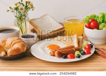 Homemade breakfast with sunny side up fried egg toast sausage fruits vegetable strawberry jam and orange juice in side view with copy space. Delicious homemade american breakfast concept for background.American breakfast on breakfast table.