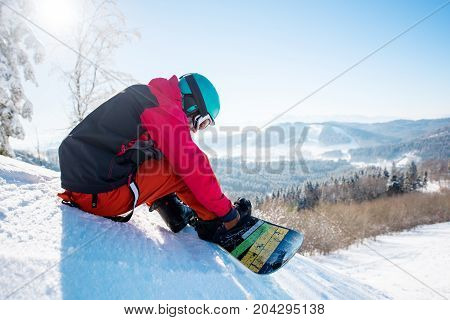 Male Snowboarder In Winter Sportswear Helmet And Skiing Mask Sitting On The Slope Preparing For Ridi