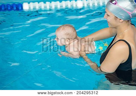 Young mother with her little son attending swimming lessons for newborns in public swimming pool