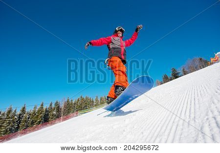 Snowboarder In The Air While Riding On The Slope In The Mountains On A Beautiful Sunny Winter Day. B