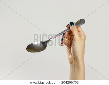 Female Hands Holding A Metal Tablespoon. Isolated On Gray Background. Closeup