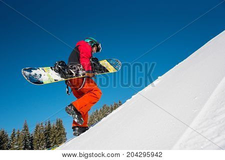 Low Angle Full Length Shot Of A Professional Snowboarder Walking Up The Slope In The Mountains, Carr
