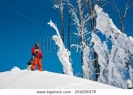 Shot Of A Snowboarder Standing On Top Of The Mountain With His Snowboard On A Sunny Winter Day Copys