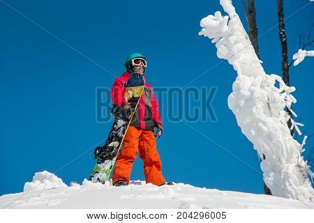 Male Snowboarder Standing On Top Of The Mountain With His Snowboard On A Sunny Winter Day At Winter