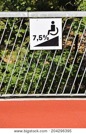 Disabled ramp sign on a metal fence