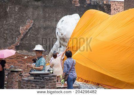 Ayutthaya Thailand - August 18 2017: Tourist praying and covering yellow robe on sleeping buddha statue in old brick temple called Wat Yai Chai Mongkol