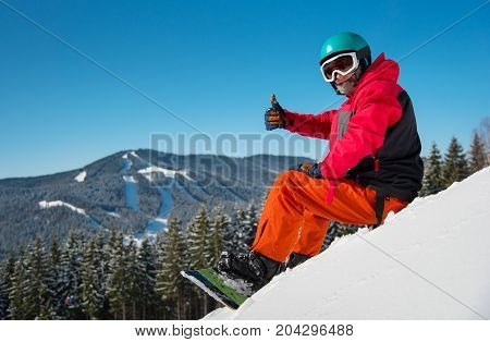 Portrait Of Male Snowboarder Sitting, Relaxing On The Snowy Slope At Winter Ski Resort In The Mounta