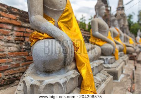 Close focus on hand of meditating monk statue in the row covered by yellow robe inside brick temple called Wat Yai Chai Mongkol in Ayutthaya of Thailand