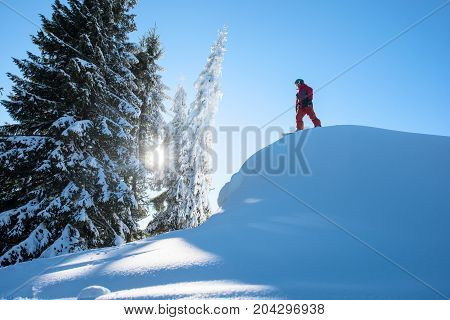 Low Angle Shot Of A Male Snowboarder Freerider Standing On Top Of The Ski Slope Preparing To Ride In