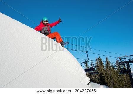 Shot Of A Happy Snowboarder Resting, Sitting In The Snow On Top Of The Mountain At Winter Ski Resort
