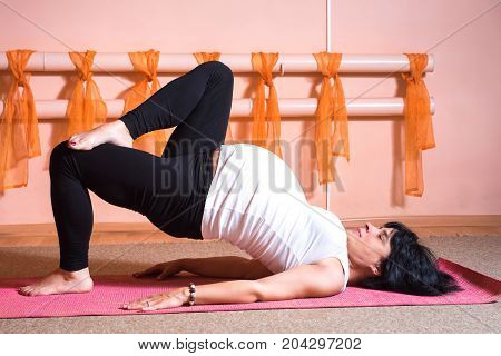 Pregnancy Yoga and Fitness concept. Healthy maternity lifestyle concept. 40 week pregnant middle aged caucasian woman doing yoga exercises laying back .