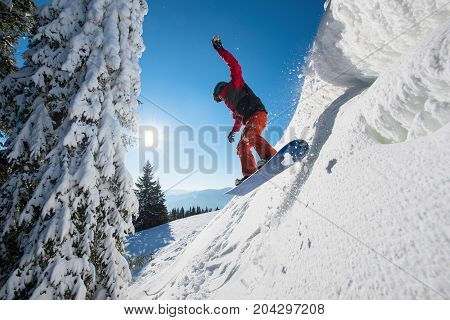 Motion Picture Of A Snowboarder Flying In The Air While Riding The Snowy Slope In Winter. Blue Sky,