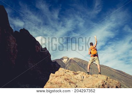 Man with arms outstretched celebrating beautiful inspiring view in mountains. Male hiker or climber with hands up enjoy inspirational landscape on rocky trail on Tenerife Canary Islands.