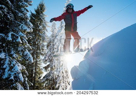 Snowboarder Flying In The Air While Skiing On The Slope In The Mountains. Sun And Blue Sky On The Ba