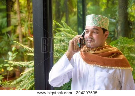 Portrait of Arab muslim man with hat and hijab onuse smart phone and look forward .