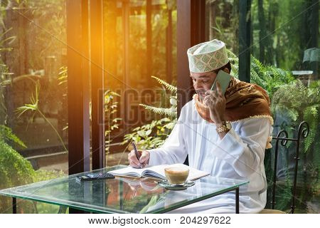 arab muslim man use smart phone and write on book in coffee shop freelance no working space lifestyle.