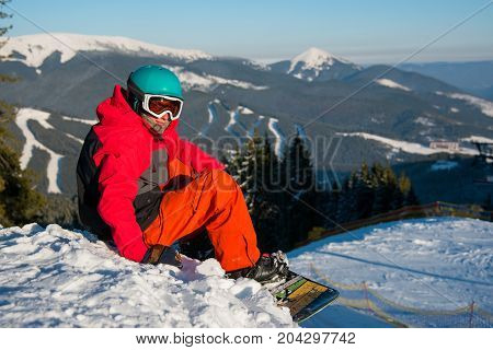 Shot Of A Male Snowboarder Resting On Top Of The Mountain, Relaxing On The Edge Of A Slope Looking T