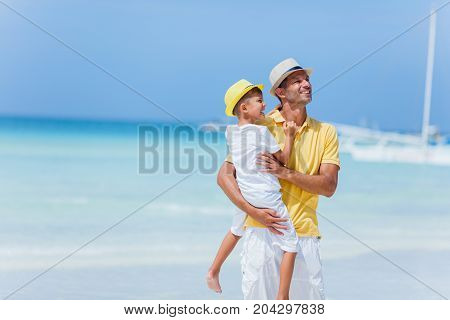 Father with his son having fun at the white sand beach
