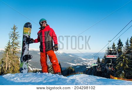 Full Length Shot Of A Snowboarder Standing With His Snowboard On The Top Of The Mountain After Ridin