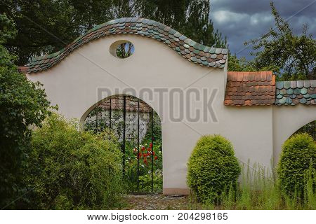 Wall of a city garden with an old tile and a black wrought iron gate