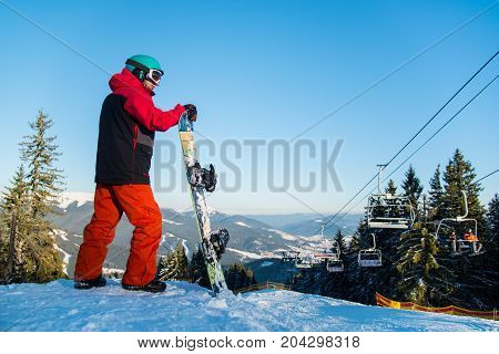 Male Snowboarder Resting With His Snowboard On Top Of The Mountain Observing Nature At Ski Resort On