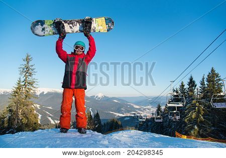 Full Length Shot Of A Snowboarder Standing On The Top Of The Mountain At Winter Ski Resort, Holding